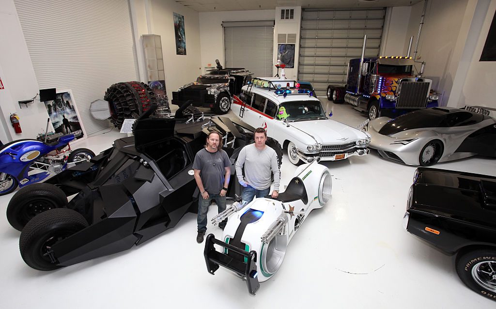 Brothers Marc and Shannon Parker stand in the middle of a garage filled with replicas of famous cars from film. The bat-mobile, Ghostbusters station wagon and  a light cycle as featured in tron stand out