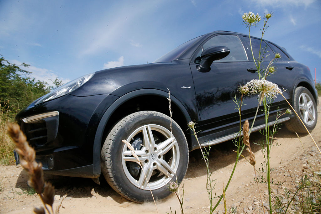 A black Porsche Cayenne driving down a dirt road