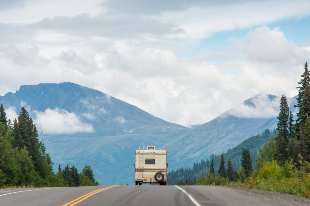 An RV drives down the road with mountains in the background