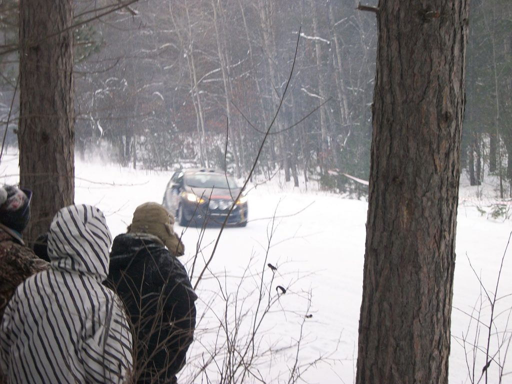 Race spectators in coats and hats at a snowy 2017 SnoDrift Rally forest stage