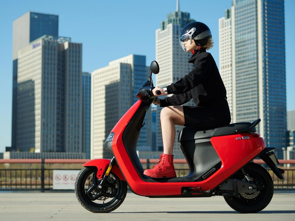 woman riding red Segway e-scooter