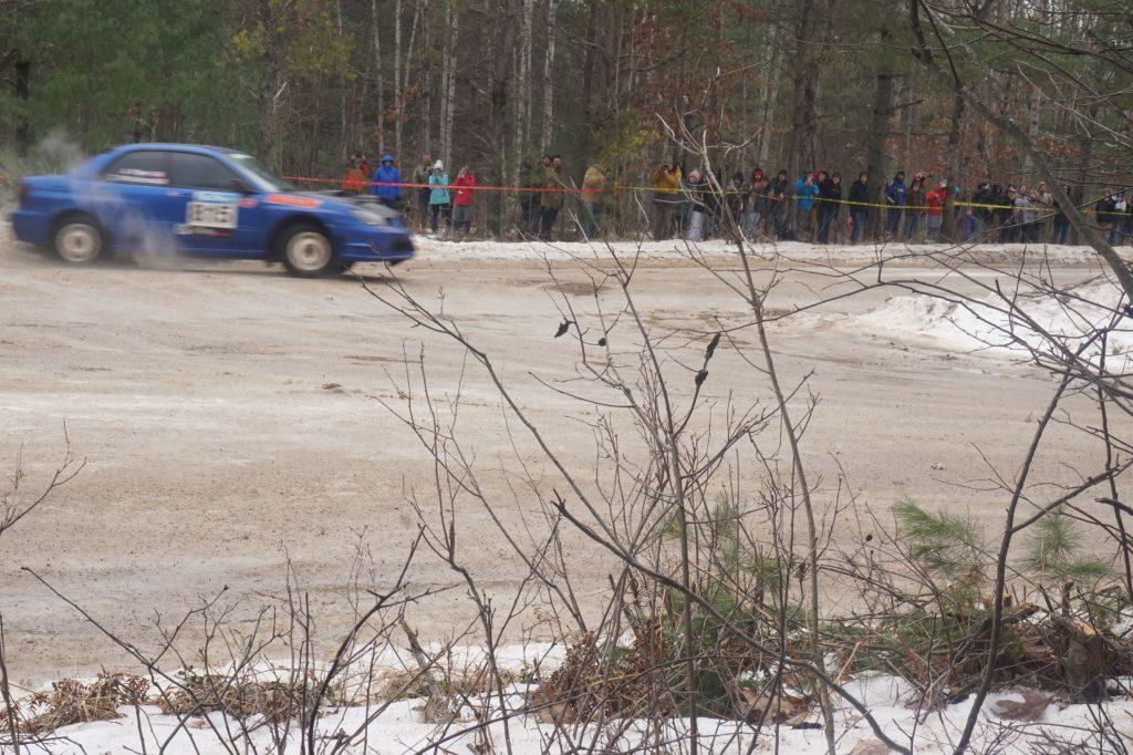 A blue Subaru Impreza WRX sliding at a 2018 SnoDrift Rally forest stage as spectators watch