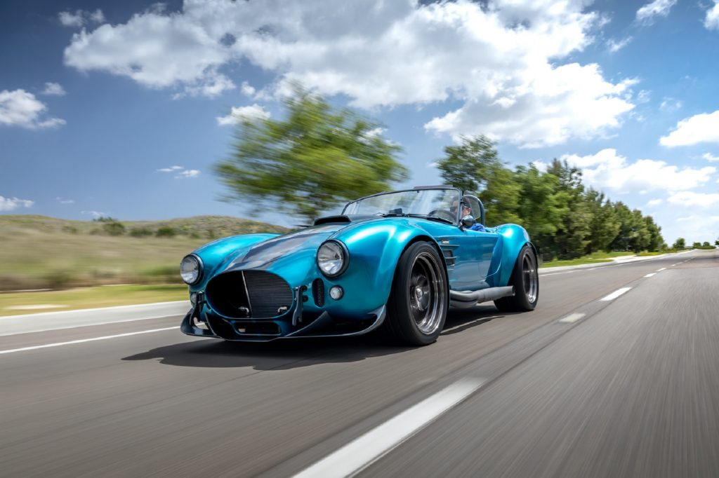 A turquoise-with-silver-stripes Superformance MKIII-R drives down the road