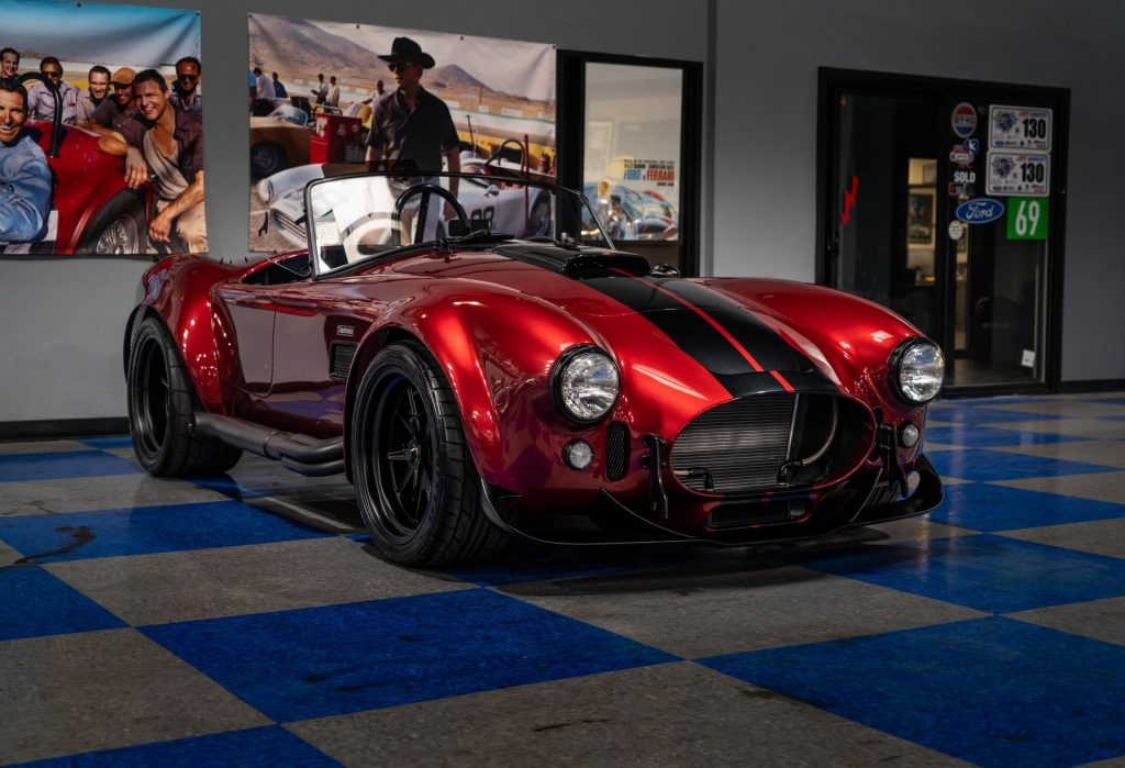 A red-with-black-stripes Superformance MKIII-R with Godzilla V8 inside a dealership