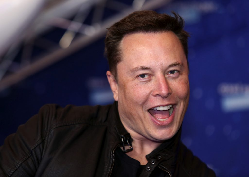 Tesla CEO Elon Musk, smiling and wearing a black moto jacket, arrives at the Axel Springer Award ceremony in Berlin, Germany, on Tuesday, December 1, 2020