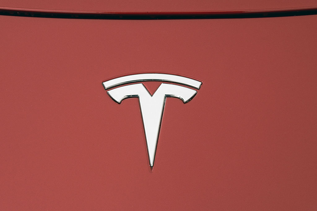 A silver Tesla logo on a red vehicle hood