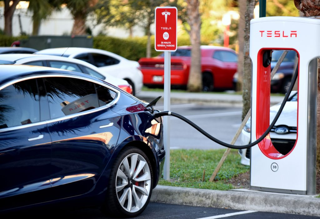 A Tesla plugs in to a Tesla branded electric vehicle charger