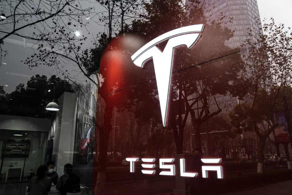 An illuminated Tesla sign seen from outside