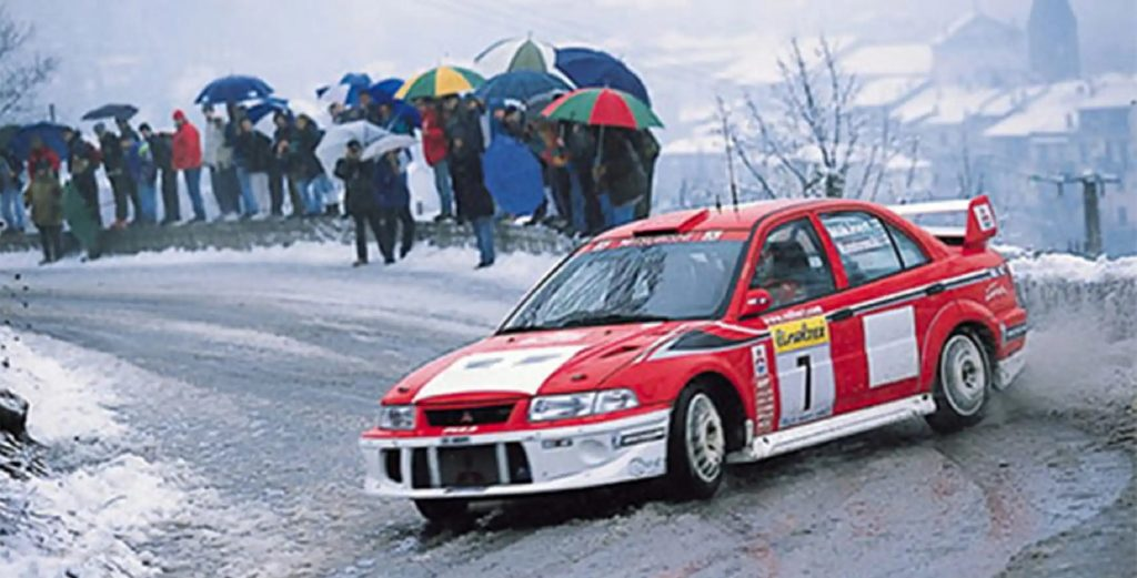 Tommi Makinen racing a red-and-white Mitsubishi Lancer Evo VI on a snowy rally stage with photographers behind him