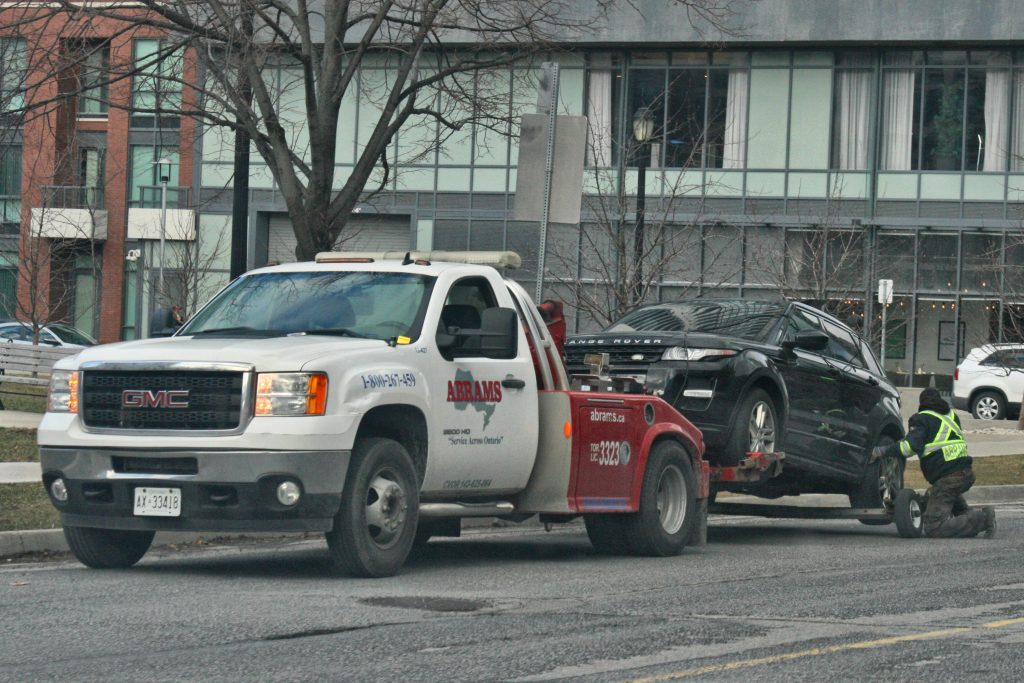 Tow truck towing a beat up Range Rover