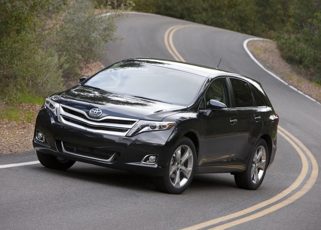 a black 2013 Toyota Venza poses in the middle of the road