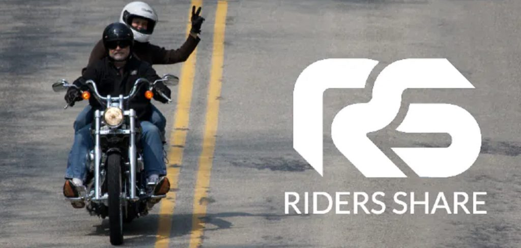 Two riders ride a rented cruiser down the road