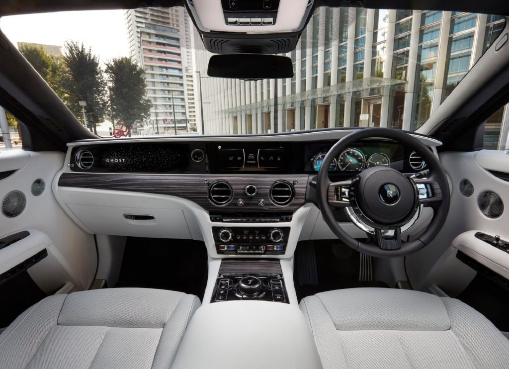 The white-leather-upholstered and wood-trimmed front interior of a UK-market 2021 Rolls-Royce Ghost