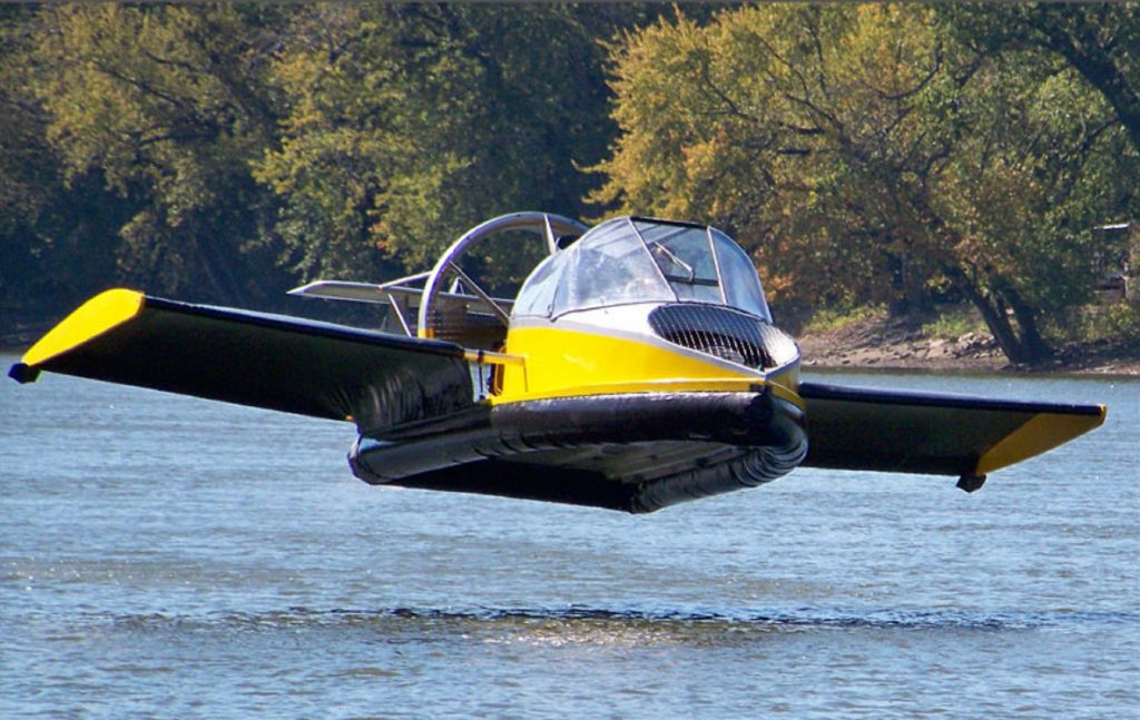 A yellow-and-black Universal Hovercraft 19XRW Hoverwing hovering over a river