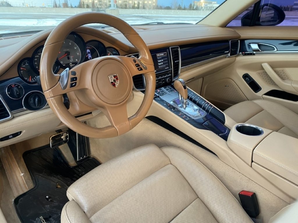 The tan-leather-covered front seats and dashboard of a used 2010 Porsche Panamera 4S