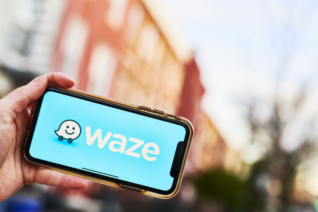 """A hand grips a smartphone. The screen has a blue background and reads """"WAZE"""" in large, white letters. The Waze logo, a smiling speech bubble on wheels, sits next to the name of the app"""