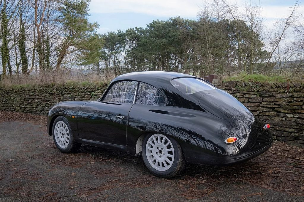The rear 3/4 view of a black WEVC Coupe development prototype on a hedge-lined road