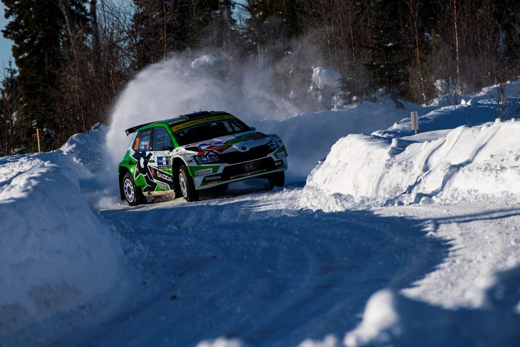 A green-and-white WRC Skoda Fabia Evo drifts through a turn at the snow-covered 2021 Artic Rally Finland