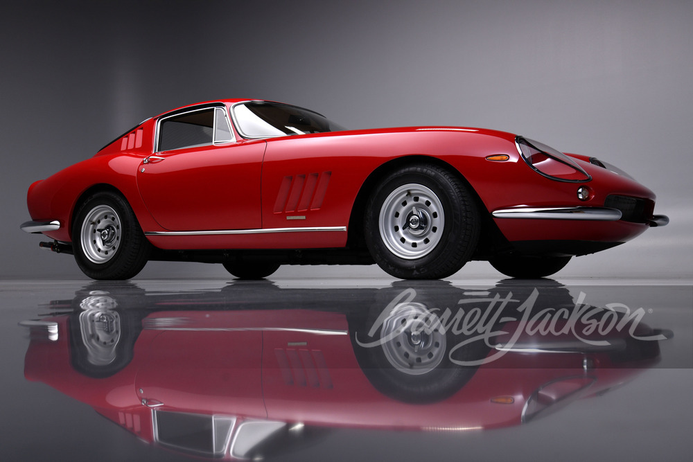 A red 1965 Ferrari 275 GTB/4 on a display with a clear reflection beneath it