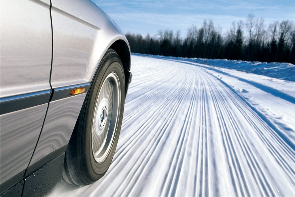 Closeup of BMW wheel rushing on a snowy road.