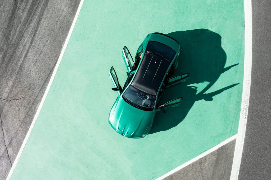 A top view of an emerald green 2021 BMW M3 on a green painted pavement