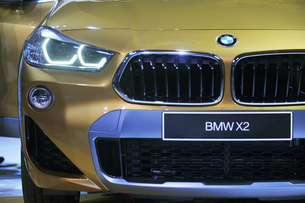 The front end of a gold bmw x2 up close