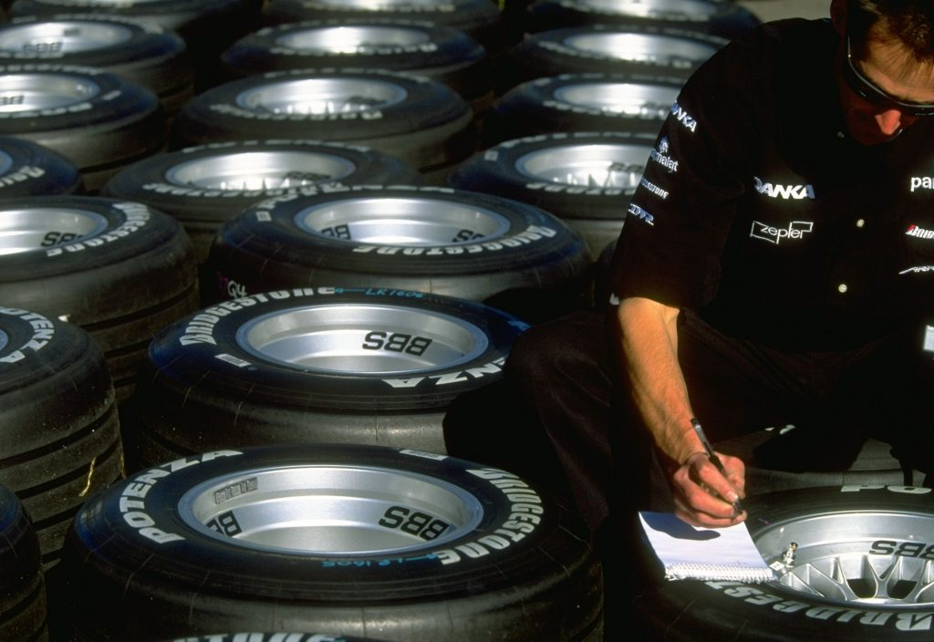 large collection of tires sitting behind a man