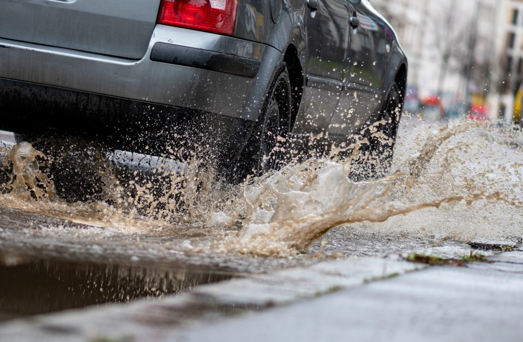 A car drives through a large puddle and potentially hydroplaning