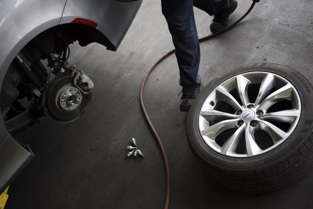 A car mechanic prepares to perform a tire rotation on a customer vehicle at a Pep Boys Company auto repair and service center in Clarksville, Indiana, on Wednesday, June 3, 2015.