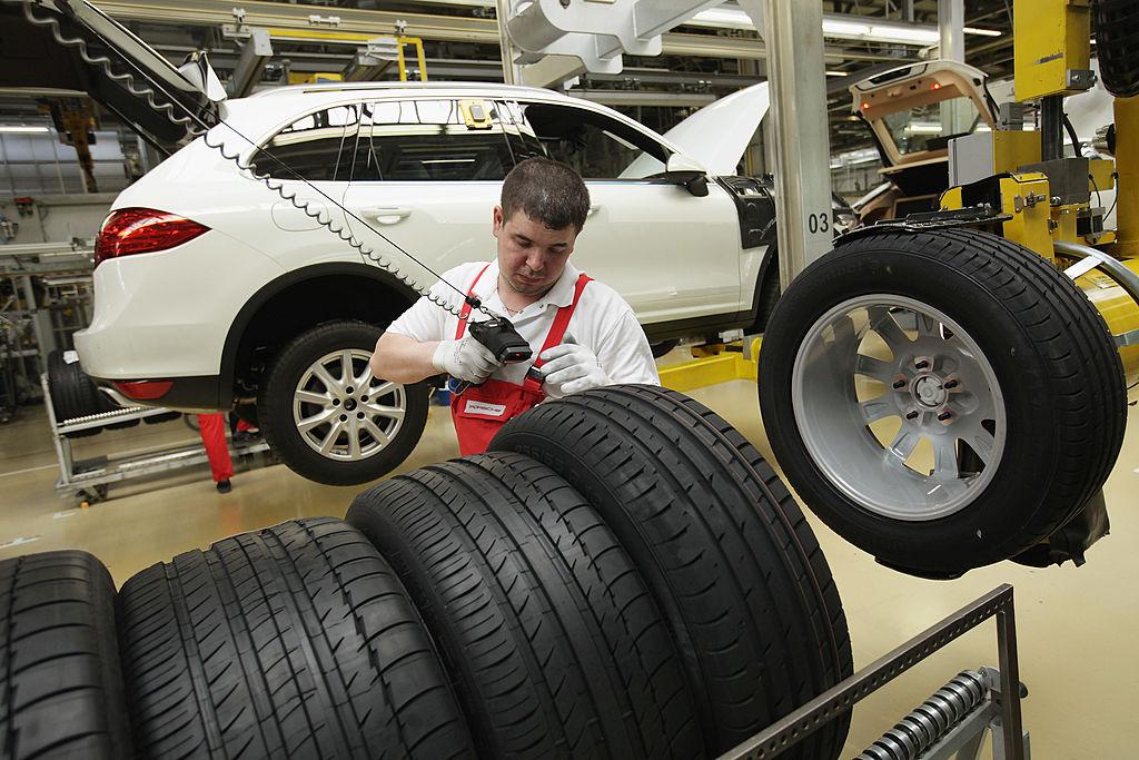 A worker assembles a white Porsche Cayenne