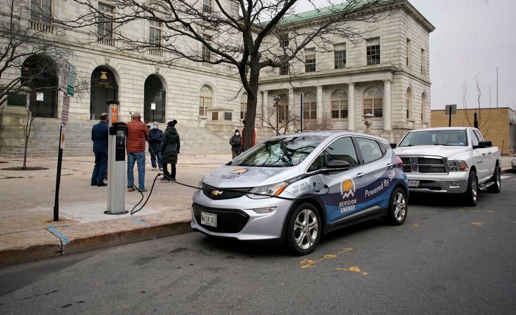 A Chevy Bolt is plugged into a new charging station in front of City Hall.