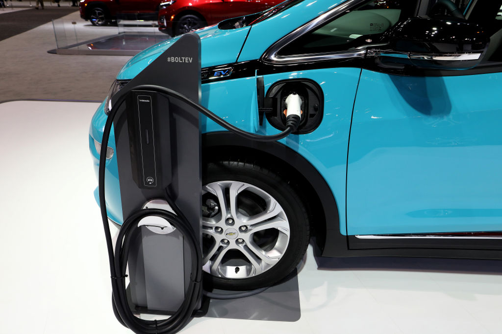A bright blue chevy bolt on display with a charging station