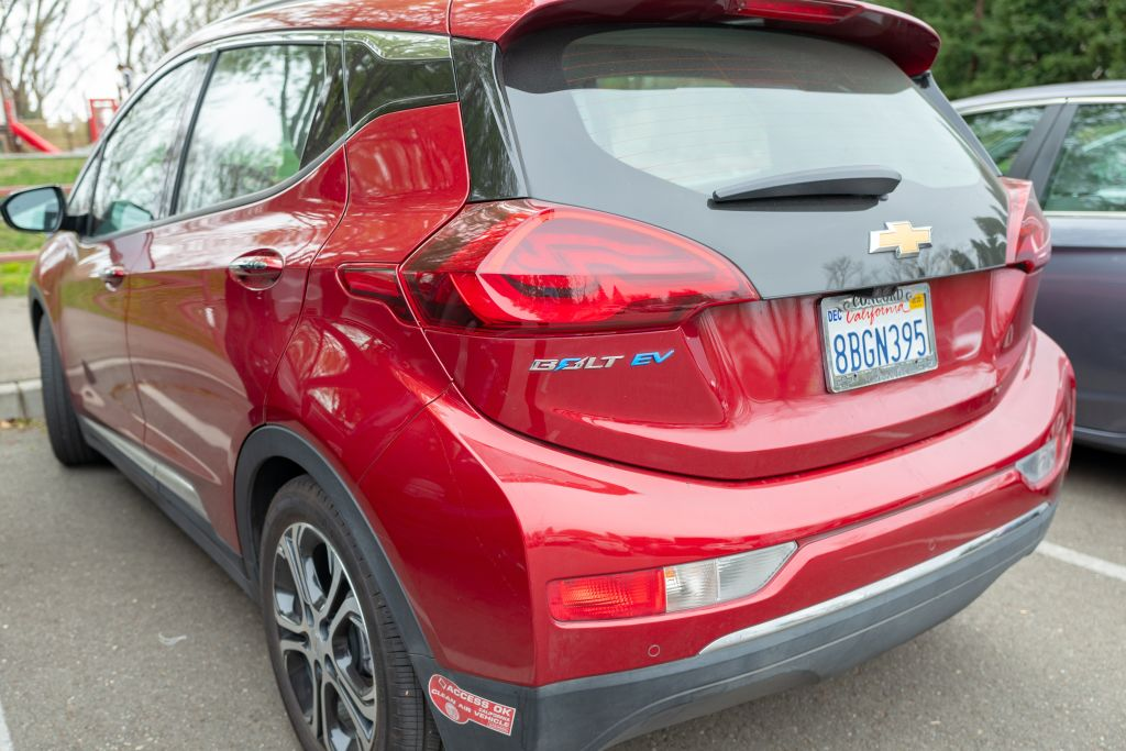 View from behind of red Chevrolet Bolt electric car, with logo and California DMV clean air access okay decal visible