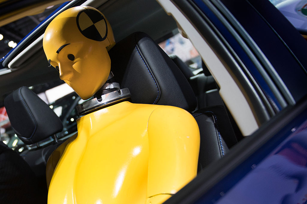 Close up through the driver's window of a yellow crash test dummy seated in a blue car