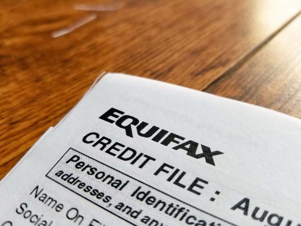 "Close-up of the upper corner of a consumer credit report from the credit bureau Equifax, with text reading ""Credit File"" and ""Personal Identification"" on a light wooden surface on September 11, 2017"