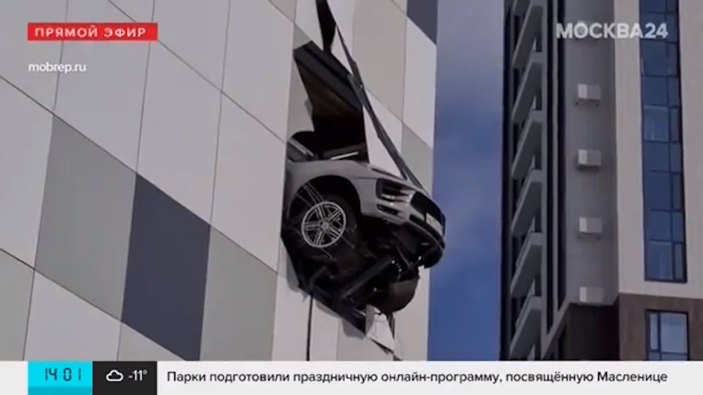 Crashed Porsche Macan hangs off the side of a building teetering on the edge