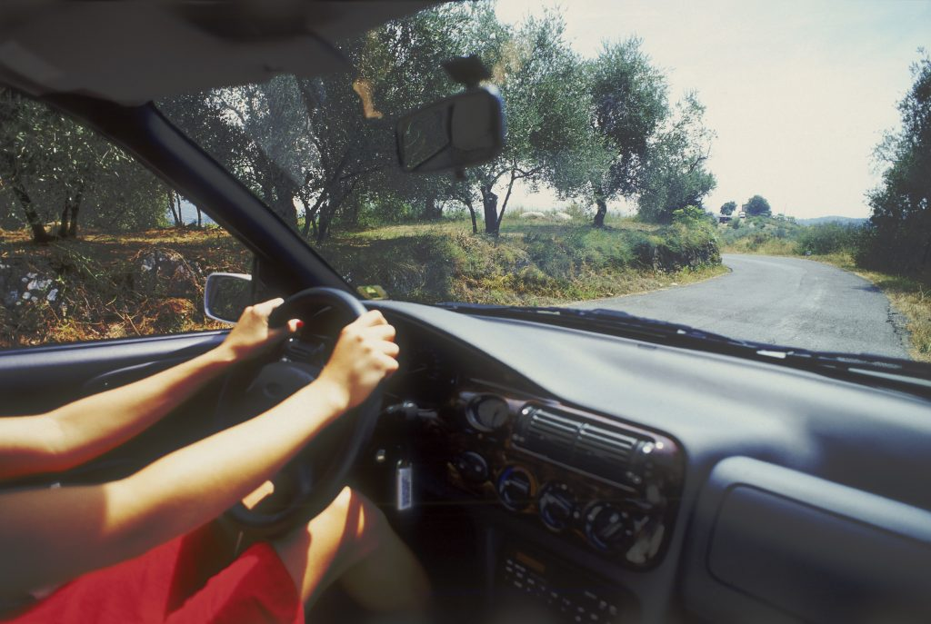 A woman driving an air-conditioned car.