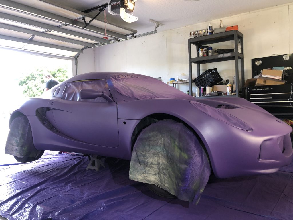 The purple base coat of Plasti Dip on my Lotus Elise as it sits on jack stands in the garage