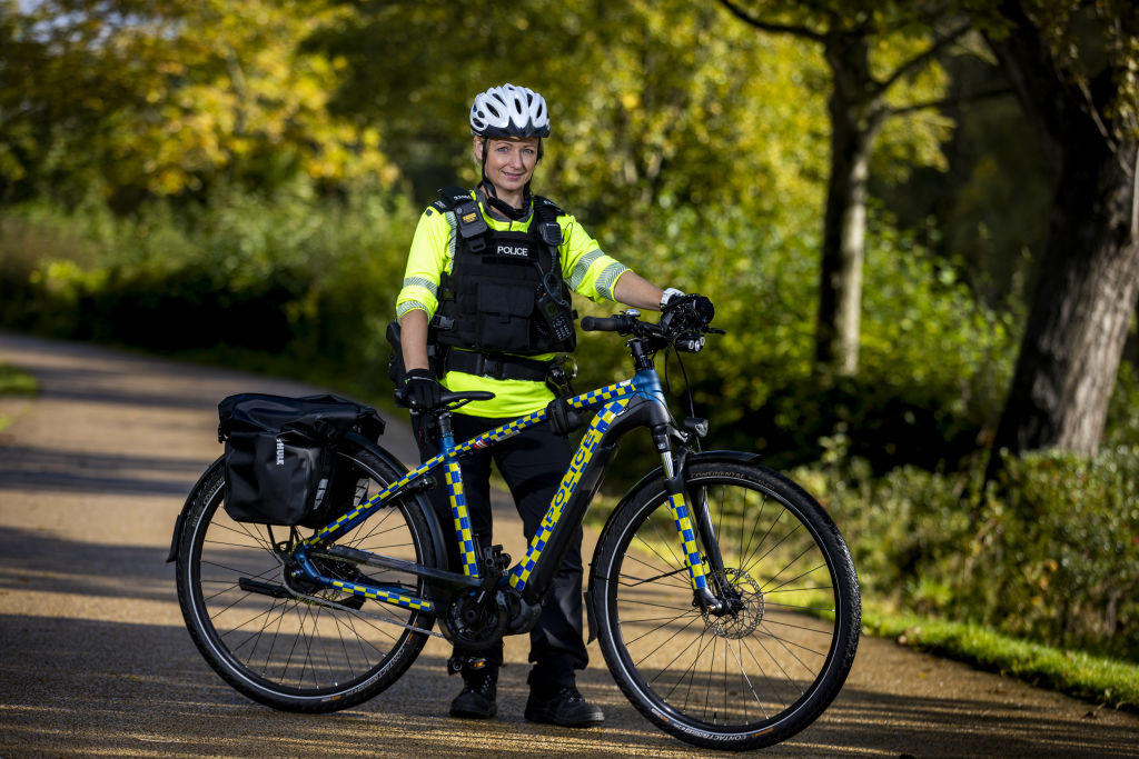 A police officer holding a new electric bike in a park