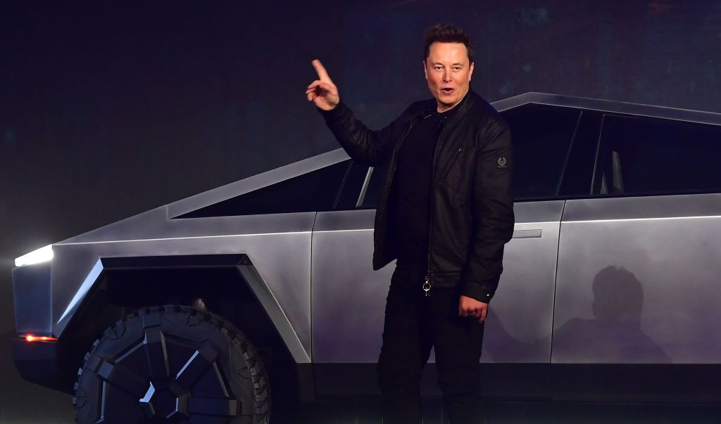 Tesla CEO Elon Musk points upward as he stands in front of a stainless steel Cybertruck