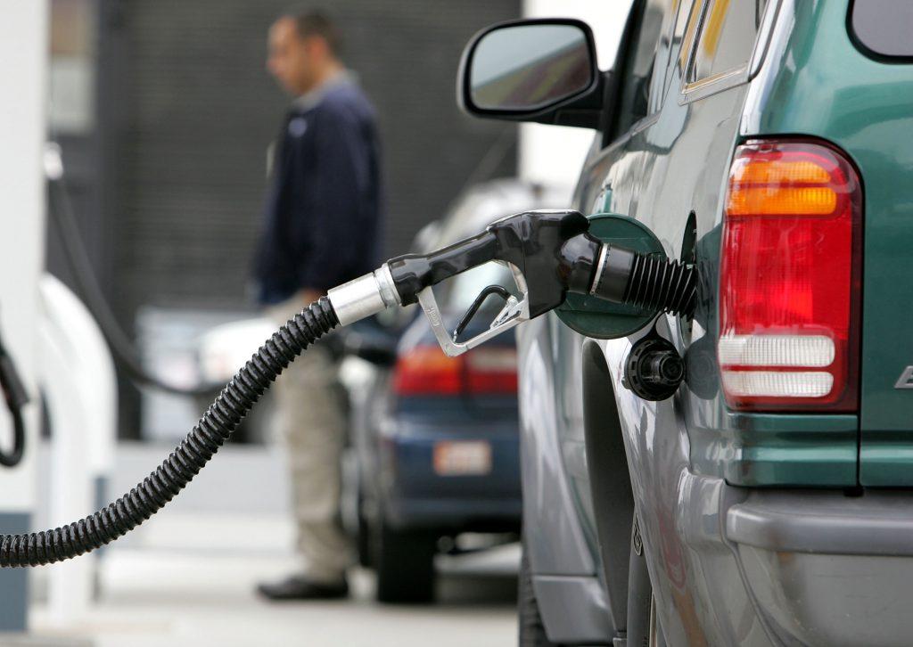 A gas pump pumps fuel into a car at a Shell service station.
