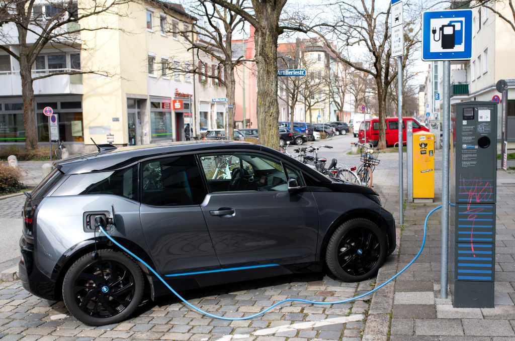 A gray BMW i3 plugged into a charging station
