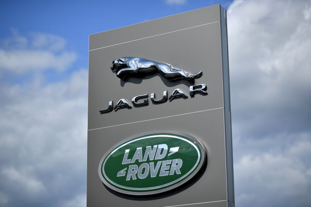 Jaguar and Land Rover dealership sign backed by a blue, partly cloudy sky
