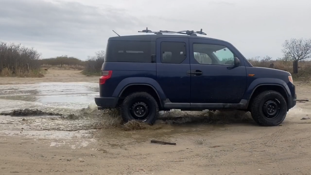 A lifted 2009 Honda Element drives through the mud
