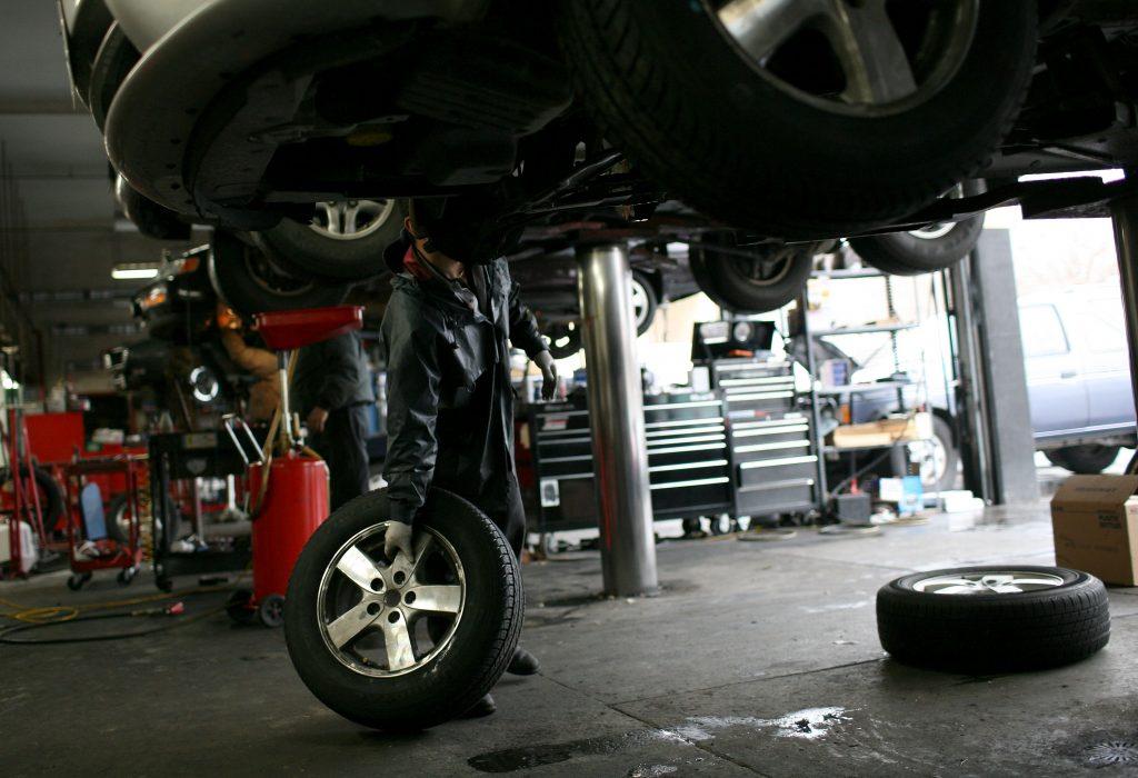 Mechanic Julio Escobedo prepares to install a tire on a Dodge Caravan.