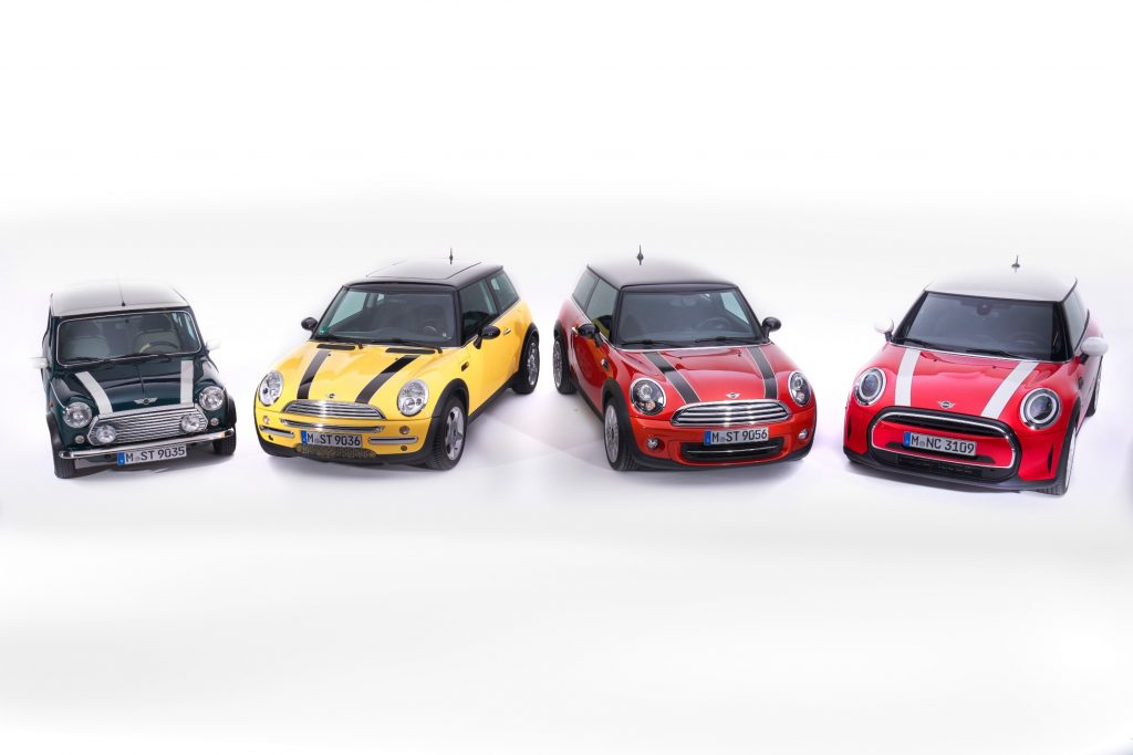 Four generations of Mini Cooper ranging from the newest model back, on a completely white background
