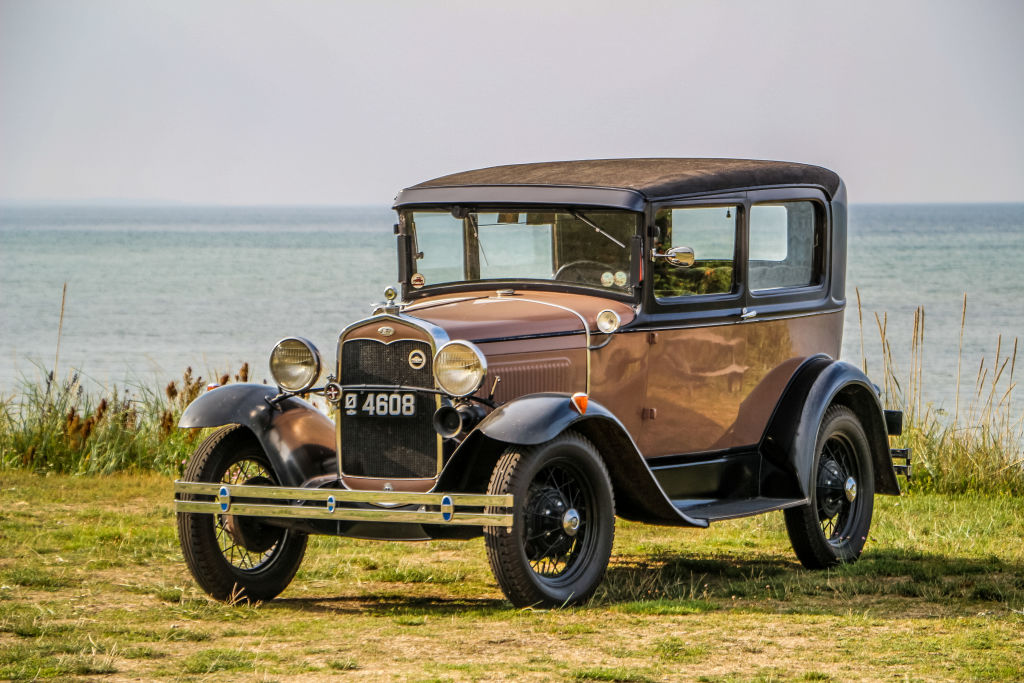 A brown Model A Ford, classic getaway car, parked on a grassy sea-side cliff
