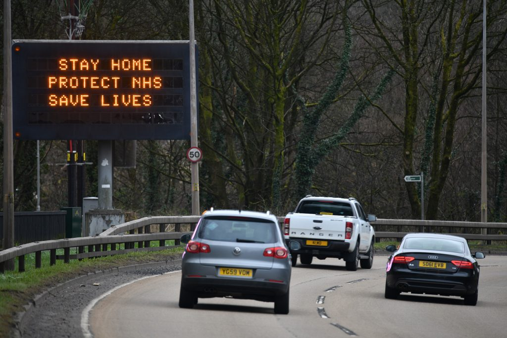 Cars drive past a sign on the A82 north bound in Glasgow, Scotland.