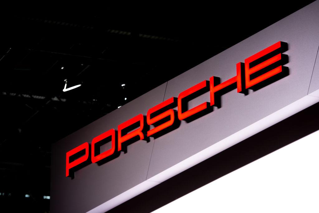A red Porsche logo over a grey background