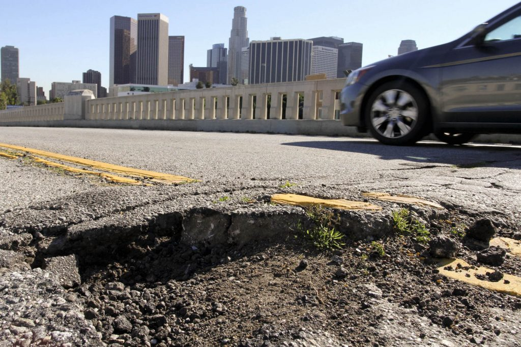 A car drives past potholes and broken asphalt on a road in Los Angeles, California, on Friday, January 21, 2011